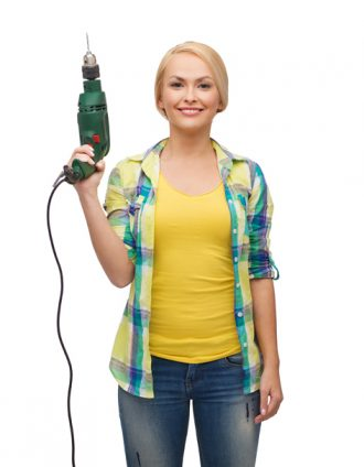 repair, construction and maintenance concept - smiling woman with drill machine